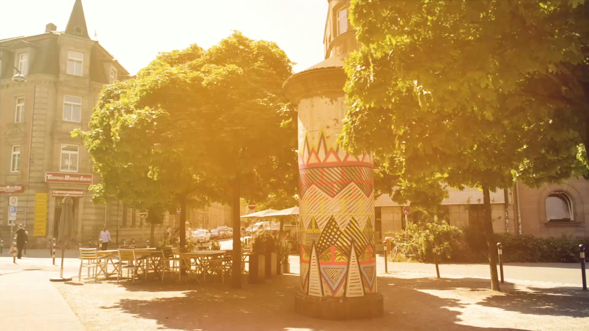 Symbolbild für den Stadteil Gostenhof in Nürnberg. Bemalte Litfasssäule bei Sonnenschein